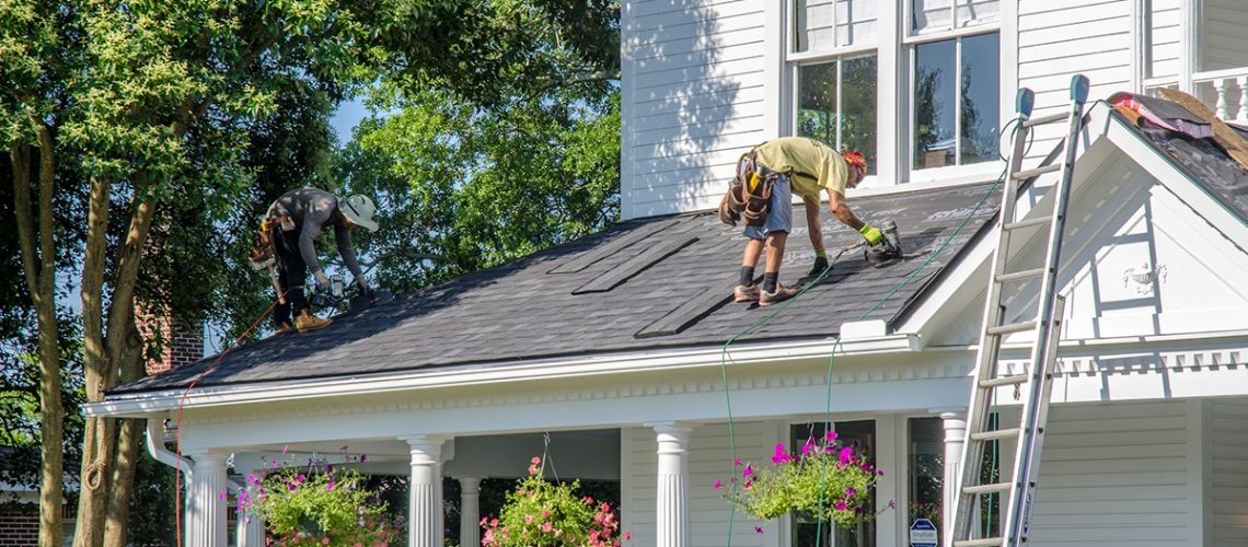 two roofers standing on a home's roof installing shingles