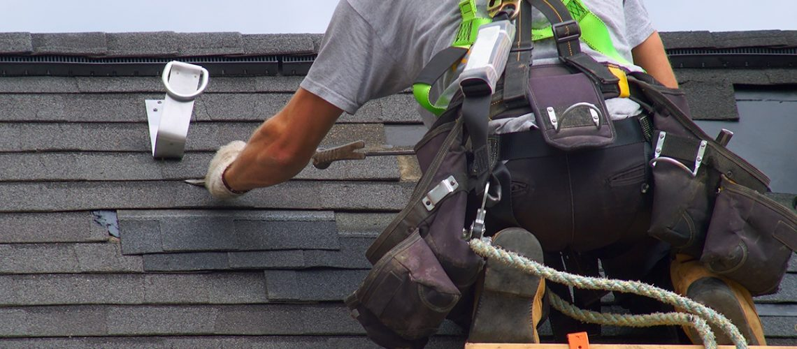 Roofer removing shingles from a home's roof
